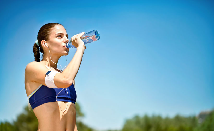 Woman Hydrating While Jogging Outdoors